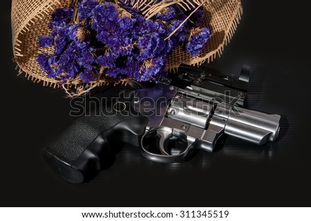 Revolvers with dot sign and violet flowers isolated on black background - stock photo