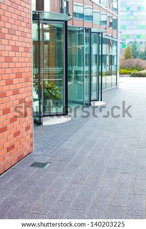 revolving glass door on a modern corporate building - stock photo