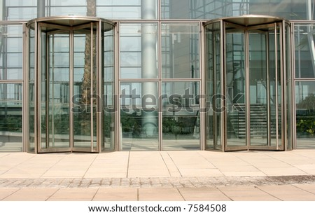 Revolving glass doors on glass walled building - stock photo