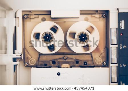 rewinding of vintage audio tape compact cassette, sepia tone - stock photo