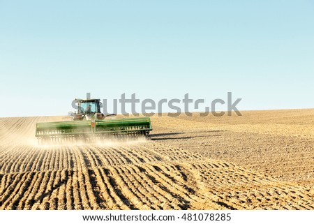Rexburg, Idaho, USA Apr. 19, 2016 Farm machinery planting rows of wheat on a windy spring day in the fertile farm fields of Idaho.