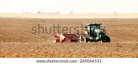 Rexburg, Idaho, USA Oct. 9, 2012- Farmers using farm machinery in the field harvesting potatoes.  The potatoes are dug, gently placed on top of undug rows of potatoes. - stock photo