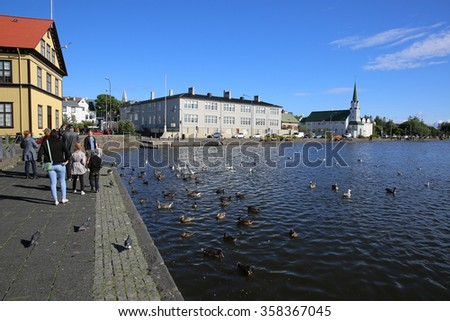 Reykjavik, Iceland - August 7, 2015: Lake Tjornin in the heart of Reykjavik. Its a popular place for Tourists and local people. The Free Church (Frikirkjan) of Reykjavik in the background  - stock photo