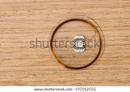 RFID Chip on Oak wood Texture with Vignette - stock photo