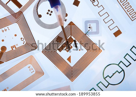RFID. Radio Frequency Identification implantation syringe and chips on Radio Frequency Identification tags, light blue background - stock photo
