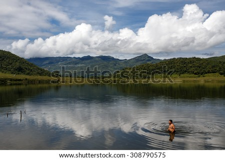 RHI LAKE, MYANMAR - JUNE 21 2015: Local man swimming at the start of the monsoon season in the recently opened to tourists Chin State region of Western Myanmar (Burma) - stock photo