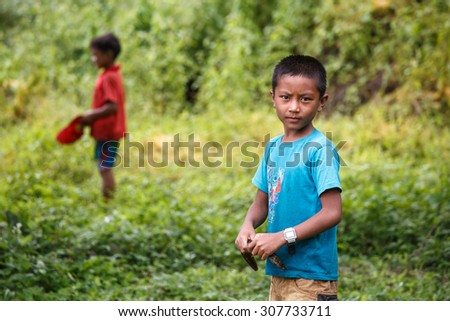 RHI LAKE, MYANMAR - JUNE 21 2015: Young boy shows his fishing catch on the shore of Rhi Lake at the start of the monsoon season in the Chin State region of Western Myanmar (Burma) - stock photo