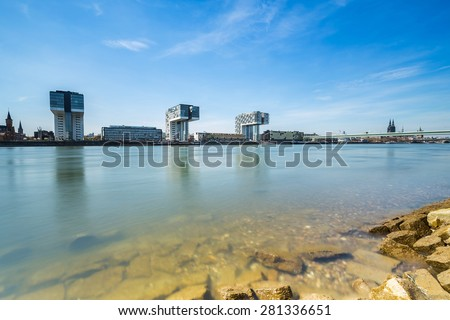 Rhine-shore in cologne with crane houses and Cathedral - stock photo