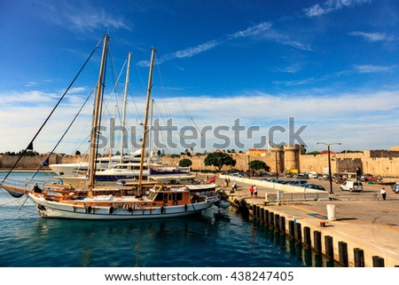 RHODES, GREECE - JUNE 11, 2016: Kolona Harbor in Rhodes with yachts and Marine Gate of the medieval fortifications. - stock photo