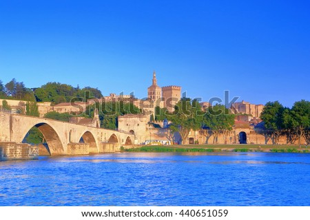 Rhone river near the bridge and distant Cathedral and Papal Palace (Palais des Papes), Avignon, Provence, France - stock photo