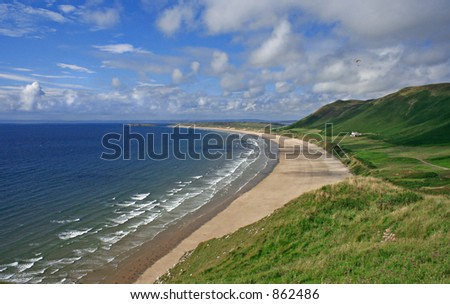 Rhossili Bay Gower South wales UK - Surf hotspot, with paraglider. No people on beach - stock photo
