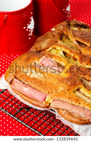 Rhubarb and custard cakes on a red background - stock photo