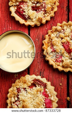 Rhubarb crumble tarts with custard on a red wooden background