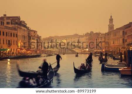 Rialto Bridge and gondolas at a foggy autumn evening in Venice. - stock photo