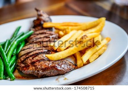 Rib eye steak served on white plate - stock photo
