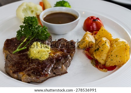 rib eye steak served with potato and salad on white dish - stock photo