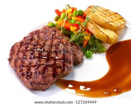 Rib-eye steak with vegetables on white - stock photo