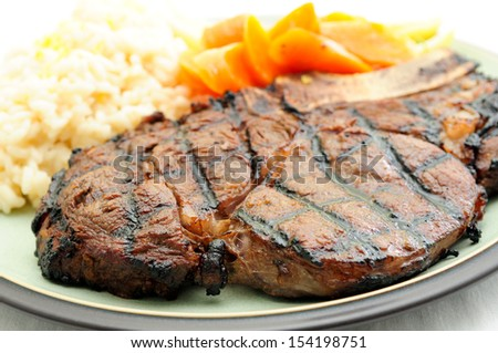 rib steak grilled to perfection with creamy risotto, carrots and yellow string beans - stock photo