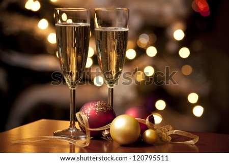 Ribbon, baubles and wine against Christmas lights - stock photo