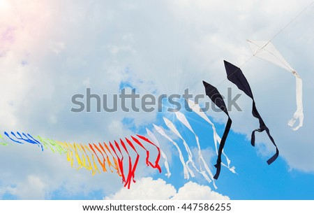 Ribbon is of multi-colored flags against the blue of the cloudy sky or kites