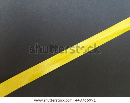 Ribbon of yellow over a black background - stock photo