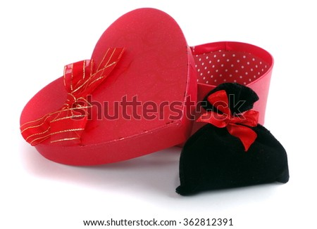 Ribboned pouch next to heart shape present box closeup isolated - stock photo