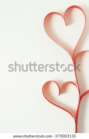 Ribbons shaped as hearts on white canvas, valentines day concept.