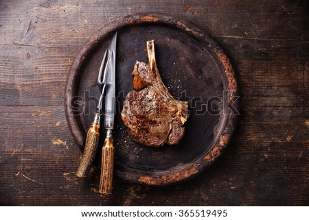 Ribeye Steak on bone and fork and knife carving set on stone plate on wooden background - stock photo