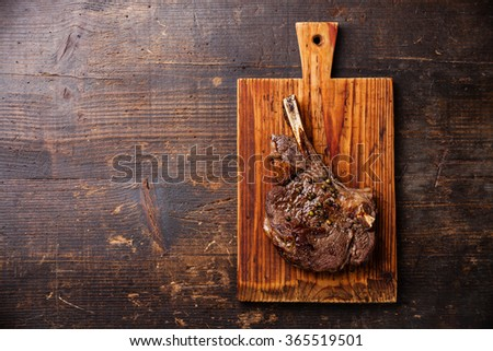 Ribeye Steak on bone with pepper sauce on dark wooden background - stock photo