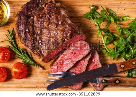 Ribeye steak with arugula and tomatoes on dark wooden background. - stock photo