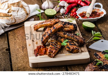 Ribs in spicy marinade with chilli, honey and beer. homemade rustic bread - stock photo