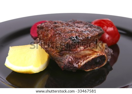 ribs on black dish over white background