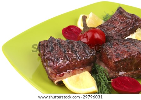 ribs on green dish over white background - stock photo