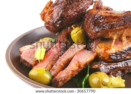 ribs on old style dish over white with green olives - stock photo