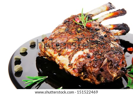 ribs rack served over black plate isolated on white - stock photo