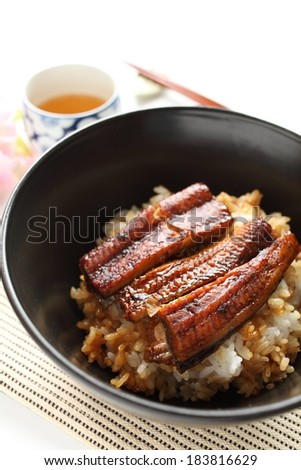 Rice and fish in a bowl beside a cup of tea and chopsticks. - stock photo