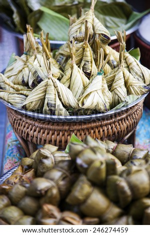 rice and meat with asian ingredient wrapped with banana leaves, THAILAND - stock photo
