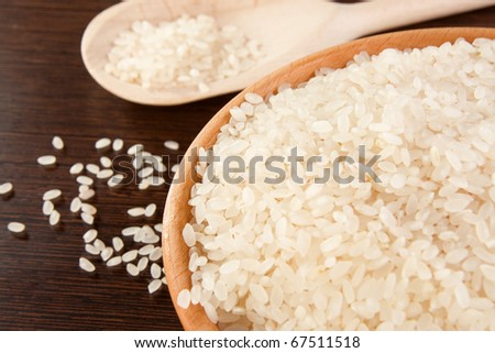 rice and wood plate with spoon on table - stock photo