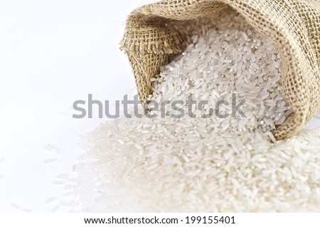 Rice Bag - close up, rice in a burlap bag on wooden surface - stock photo