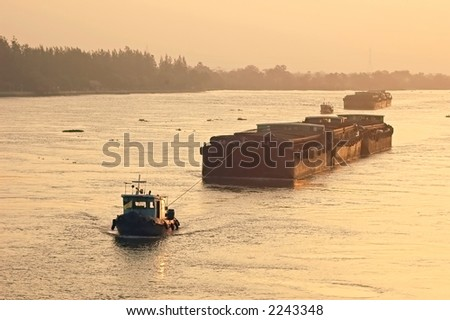 Rice barge getting tugged up a Thai river - stock photo