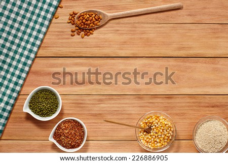 Rice Beans Corn and Sesame seeds in a white Bowl and wooden spoon on wood background with a Table Cloth. Healthy grain food selection with Text Space - stock photo