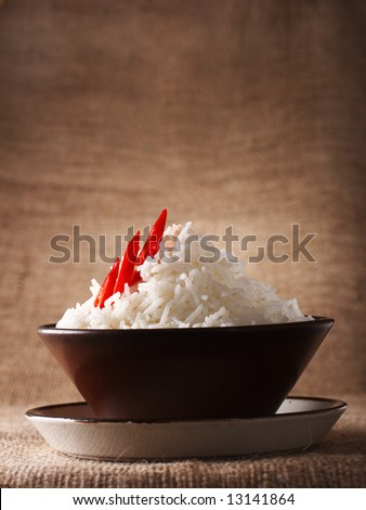 rice bowl with fresh chillies on brown rustic background, Low Key Lighting Technique, Shallow DOF - stock photo