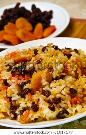 Rice, carrots and dried fruits. - stock photo