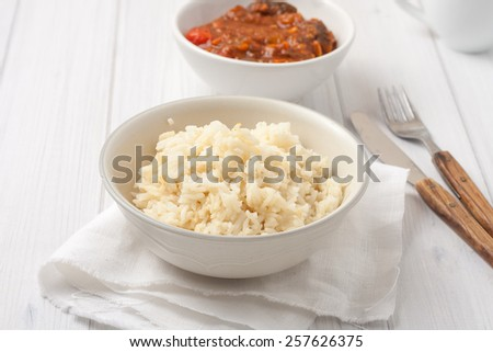 rice cooked in chicken stock in a bowl with a side of stewed veggies - stock photo