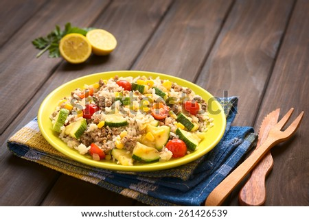 Rice dish with mincemeat and vegetables (sweet corn, cherry tomato, zucchini, onion) served on plate, photographed on dark wood with natural light (Selective Focus, Focus in the middle of the dish) - stock photo