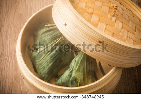 rice dumpling wrapped in bamboo leaves and steaming basket - stock photo
