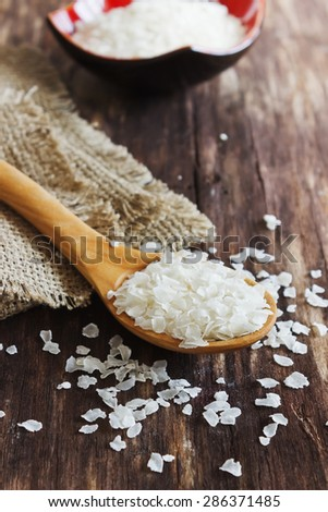 rice flakes in a wooden spoon on the old wooden background.health and diet food. selective focus - stock photo