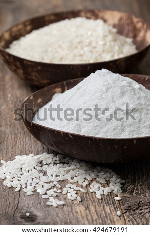 rice flour in a wooden bowl, rice on the old wooden background - stock photo