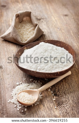 rice flour in a wooden bowl, rice on the old wooden background. gluten-free - stock photo