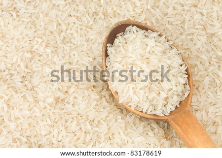 rice grain and wood spoon - stock photo